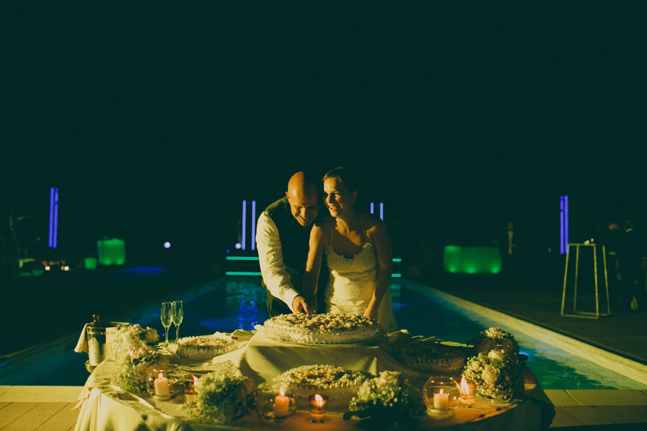 cutting the cake next to the sweeming pool